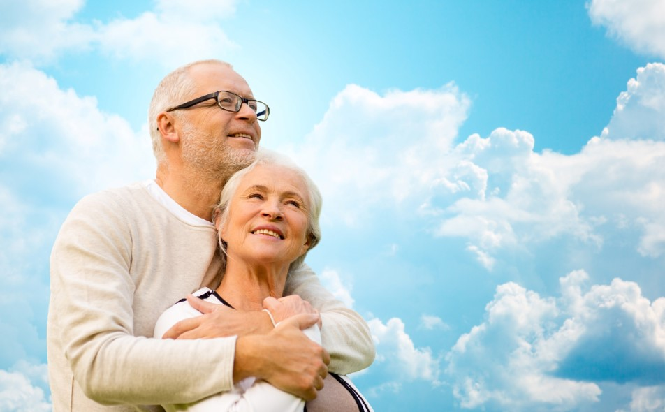 family, age, love, relations and people concept - happy senior couple hugging over blue sky and clouds background